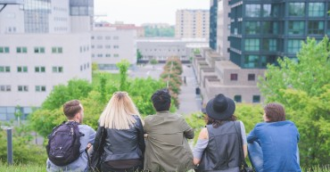 Group of young multiethnic friends sitting in a park, seen from behind, looking at the horizon - future, prospective, friendship concept